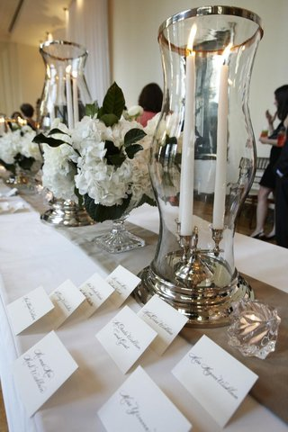 seating-card-table-with-crystal-glass-vases-and-white-flowers