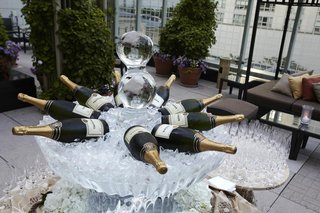 ice-sculpture-carved-like-fountain-with-large-champagne-bottles