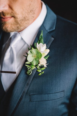 navy-blue-groom-suit-with-green-and-white-boutonniere