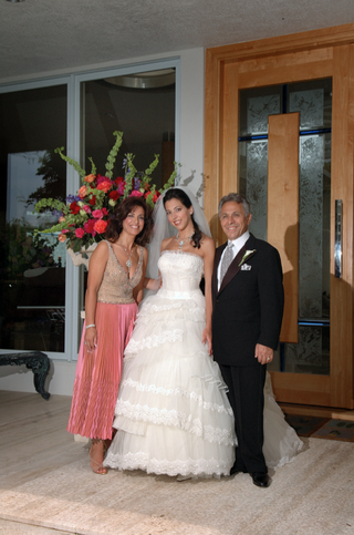 bride-with-mother-and-father-in-front-of-flower-arrangements