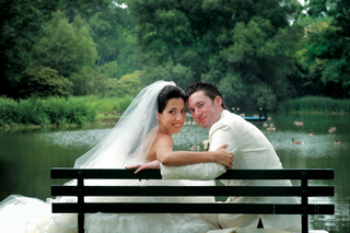 couple-on-park-bench-in-front-of-pond-with-a-number-of-goose
