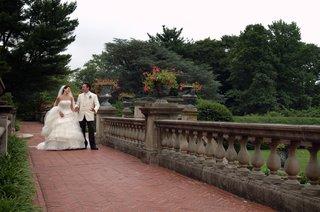 bride-and-groom-walk-through-green-venue-grounds
