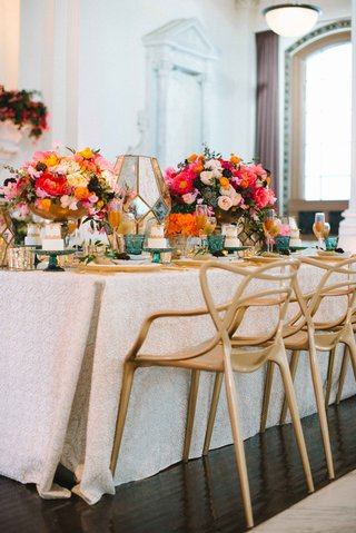 long-tablescape-gold-chairs-white-table-linen-colorful-flowers