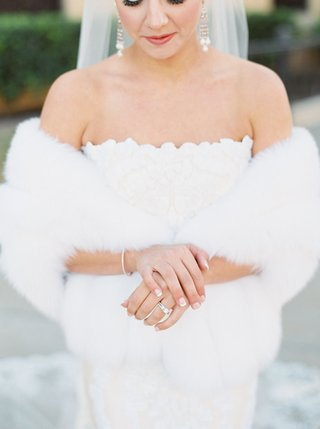 bride-in-strapless-romona-keveza-gown-with-chandelier-earrings-bracelet-wedding-ring-french-manicure