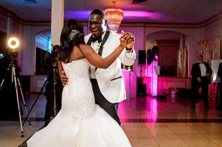 bride-in-strapless-wedding-dress-trumpet-gown-with-groom-in-white-tuxedo-jacket-bright-pink-lighting