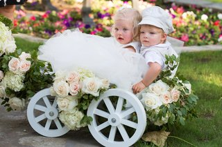 blonde-flower-girl-and-ring-bearer-in-white-wagon-with-rose-decorations