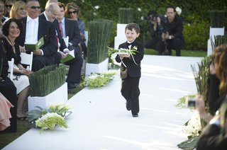 ring-bearer-walking-down-white-aisle-lined-with-bamboo