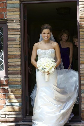 bride-walks-out-of-suite-in-white-bridal-gown-with-bouquet