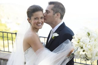groom-kisses-bride-on-cheek-on-wedding-day
