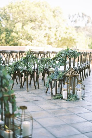 eucalyptus-garland-connect-rows-of-chairs-at-ceremony-lanterns-at-aisle
