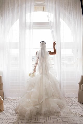 bride-in-matthew-christopher-trumpet-gown-with-cathedral-veil-bouquet-looking-out-window-city-weddin