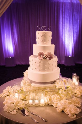 four-layer-white-wedding-cake-with-heart-design-and-purple-sugar-flower-ribbon-white-flowers-lucite