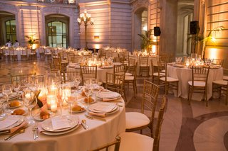wedding-reception-tables-with-candles-in-hurricanes-pink-petals-gold-chiavari-chairs