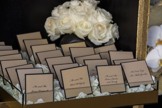 wedding-reception-escort-cards-trays-with-white-rose-petals-gold-and-black-border-seating-cards-rose