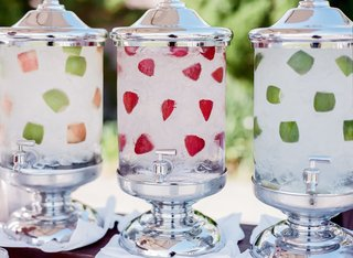 outdoor-cocktail-hour-with-glass-silver-water-dispensers-with-apples-strawberries-limes