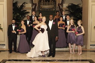 bride-in-an-amsale-high-low-gown-groom-in-black-tuxedo-and-bridesmaids-in-dark-purple-dresses