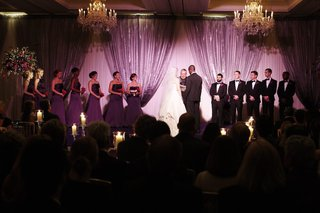 wedding-ceremony-in-a-ballroom-with-purple-lighting-and-candlelight