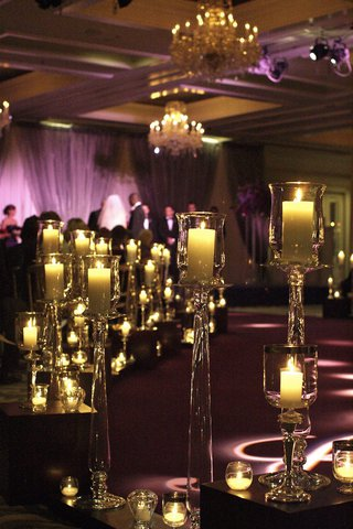 wedding-ceremony-in-a-ballroom-with-purple-lighting-and-lots-of-candles-in-crystal-containers