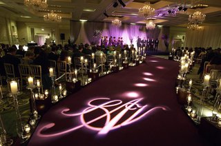wedding-ceremony-aisle-with-dark-purple-carpet-projected-monogram-and-candles-in-crystal-vessels