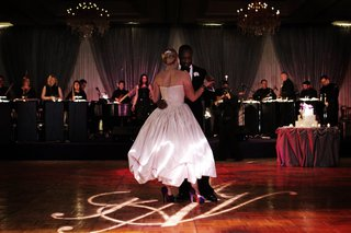 bride-in-a-strapless-amsale-gown-dances-with-groom-in-black-tuxedo