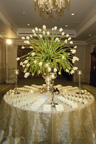 wedding-reception-place-card-table-with-a-centerpiece-of-white-tulips-and-candles