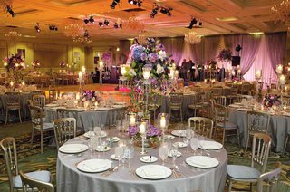 wedding-reception-tables-covered-in-silver-tablecloths-and-candelabra-centerpieces-of-purple-flowers