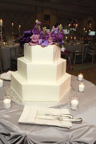 white-cake-with-octagon-shaped-layers-and-topped-with-purple-flowers
