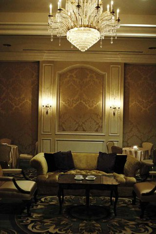 wedding-lounge-area-with-a-chandelier-golden-wallpaper-and-furnishings