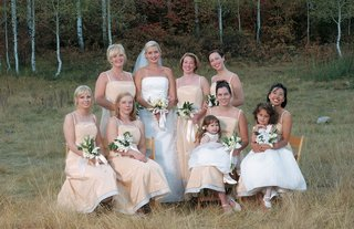 bride-with-bridesmaids-on-chairs-in-countryside