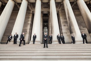 men-in-tuxedos-standing-on-stairs-next-to-columns