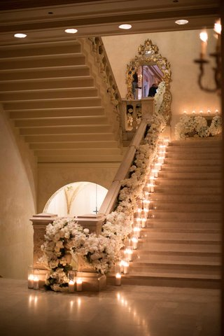 wedding-at-the-plaza-hotel-candles-on-staircase-mirror-white-flower-runner-down-railing