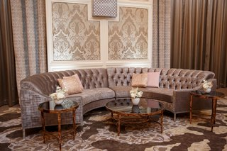 wedding-reception-curved-semi-circle-sofa-settee-pink-pillows-gold-tables-lounge-area-damask-print