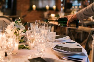 wedding-reception-round-table-linens-with-cut-crystal-glassware-server-pouring-champagne-into-glass