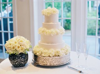 white-four-layer-wedding-cake-fresh-flower-decorations-on-silver-stand-next-to-bouquet-of-roses