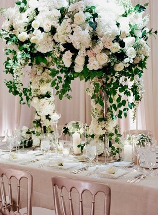 tall-wedding-reception-centerpiece-on-rectangle-table-silver-chairs-candles-in-glass-vessels