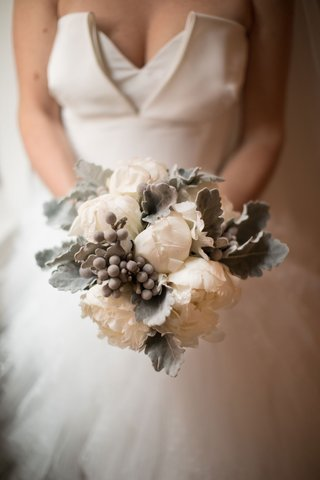 bride-holding-white-peony-with-silver-brunia-balls-dusty-miller-winter-wedding-bouquet-ideas