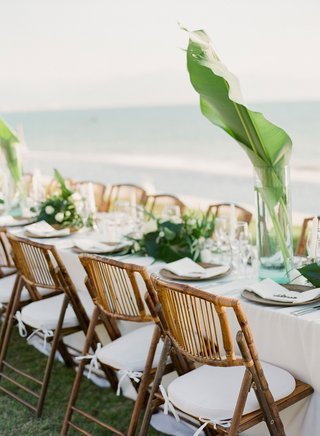 wedding-reception-overlooking-beach-and-ocean-white-table-wood-vintage-looking-chair-green-leaves