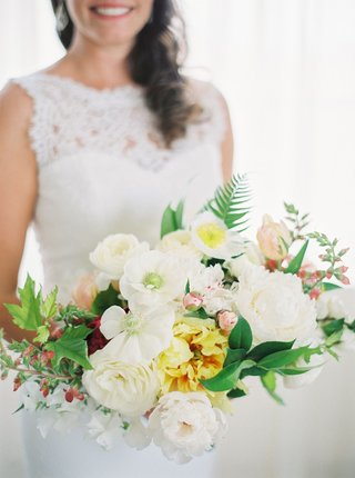bride-in-lace-wedding-dress-holding-bouquet-of-white-flowers-yellow-flowers-ferns-greenery