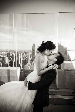 black-and-white-photo-of-chinese-american-bride-and-groom-kissing-with-view-of-new-york-city-skyline