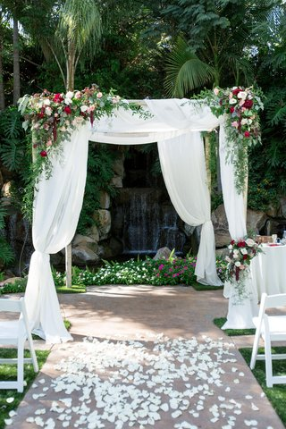 chuppah-with-greenery-and-red-blush-and-ivory-florals-rose-petal-aisle-waterfall