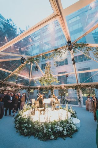 wedding-cocktail-hour-string-musicians-quartet-on-white-stage-greenery-flowers-chandelier-open-tent