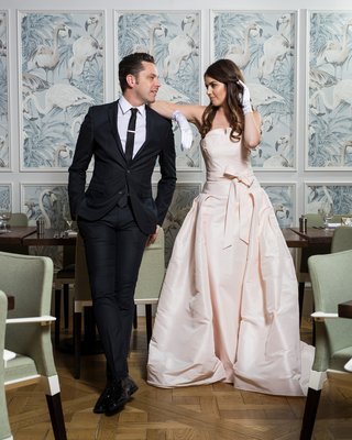 bride-in-le-spose-di-gio-blush-gown-and-white-gloves-leaning-on-shoulder-of-groom