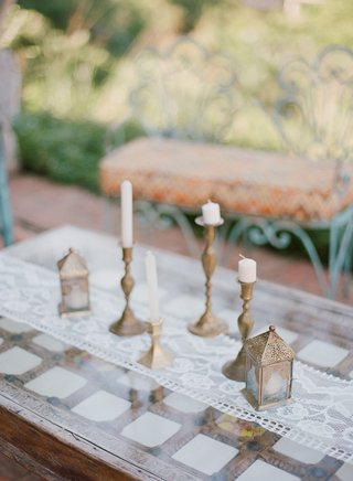 wedding-rehearsal-dinner-welcome-party-wood-table-with-white-lace-runner-bronze-lantern-and-candles