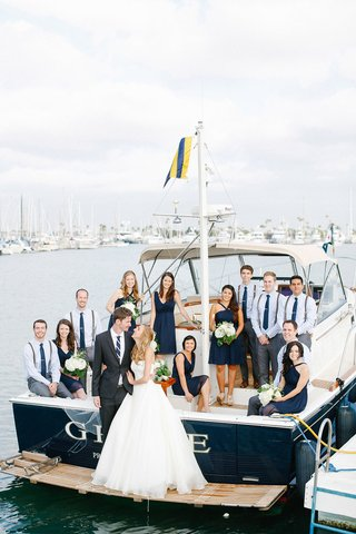 bride-and-groom-with-nautical-blue-wedding-party-on-family-boat-in-bay-in-san-diego