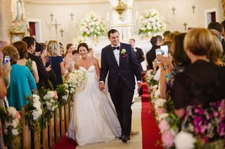 bride-in-legends-romona-keveza-wedding-dress-holding-groom-hand-walking-up-aisle-ceremony-church