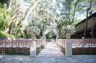 wedding-ceremony-outdoor-venue-stone-aisle-flower-petals-tall-risers-blush-rose-gold-chairs