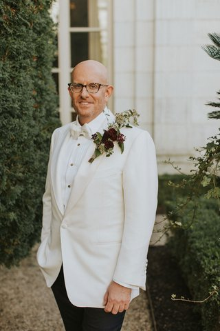 groom-in-white-tuxedo-jacket-bow-tie-with-large-boutonniere-burgundy-flower-greenery-statement