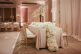 wedding-reception-in-ballroom-with-kings-table-candelabrum-and-lush-flower-centerpiece-flowing