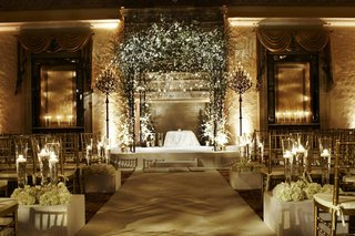 candlelit-indoor-jewish-ceremony-with-white-decorations