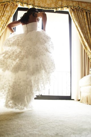 bride-walks-toward-bridal-suite-window-in-wedding-dress